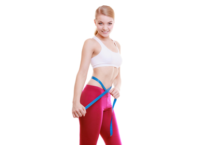 Fitness girl measuring her waistline isolated. Weight loss.