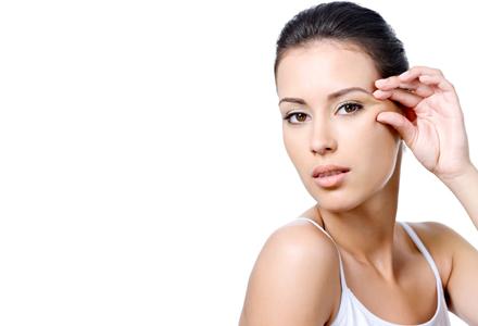 Woman with sensual look pinching skin near the eye