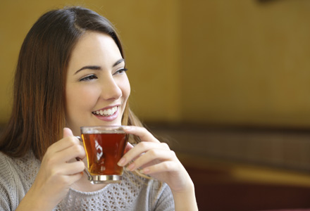 Happy woman thinking holding a cup of tea in bar